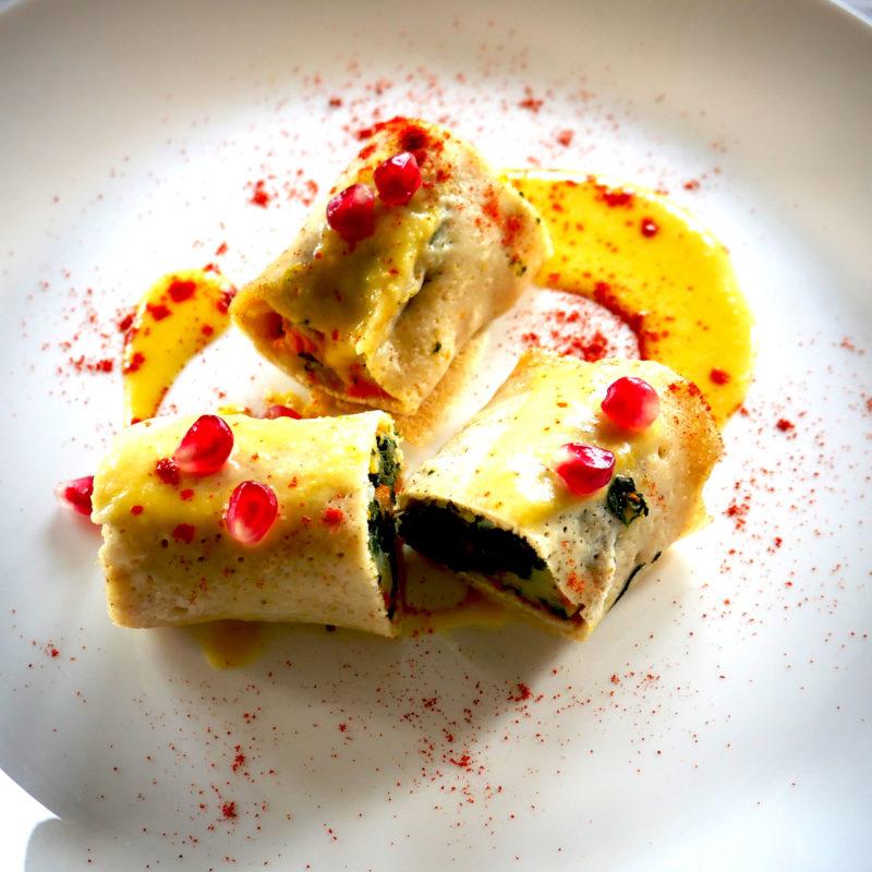 Crepes salate al forno farcite con zucca e bietole, guarnite con crema di ceci e chicchi di melagrana, paprika dolce