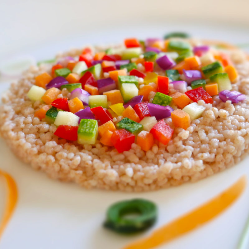 Vegan spelled cous cous with colorful vegetables